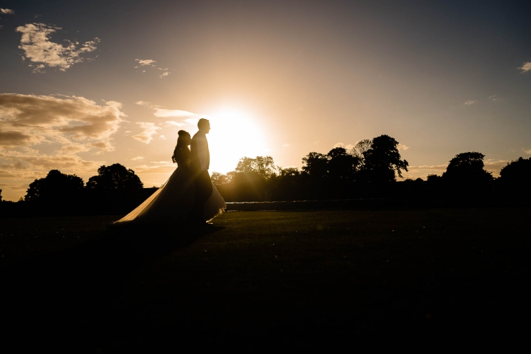 Bride and groom walk together in the sunset
