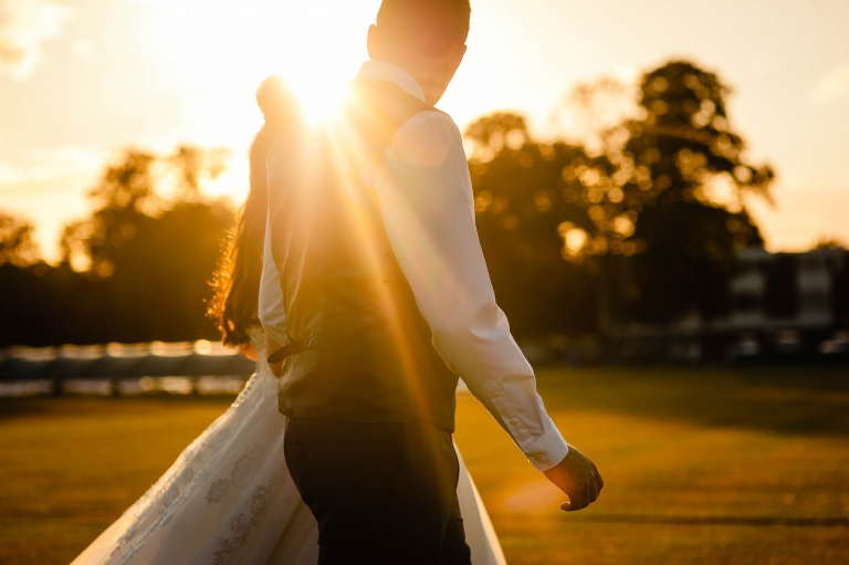 Bride and groom hold hands in the sunset