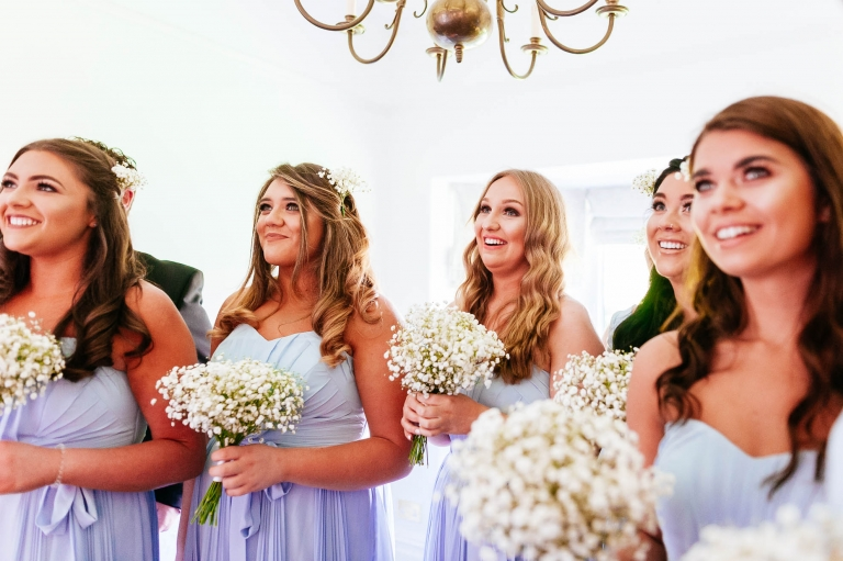 bridesmaids smile as they see the bride in her dress for the first tiime
