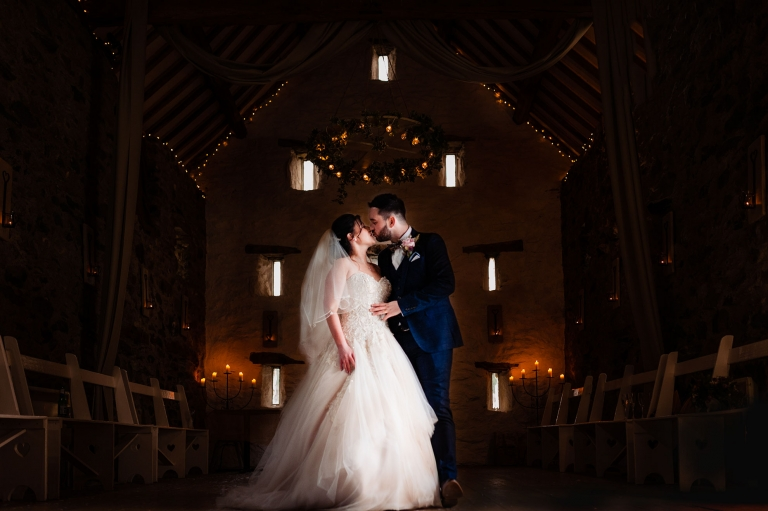 Bride and groom kiss in barn