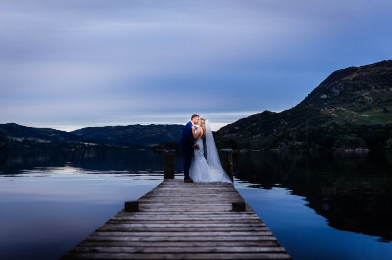 Bride and groom kiss on lake jetty