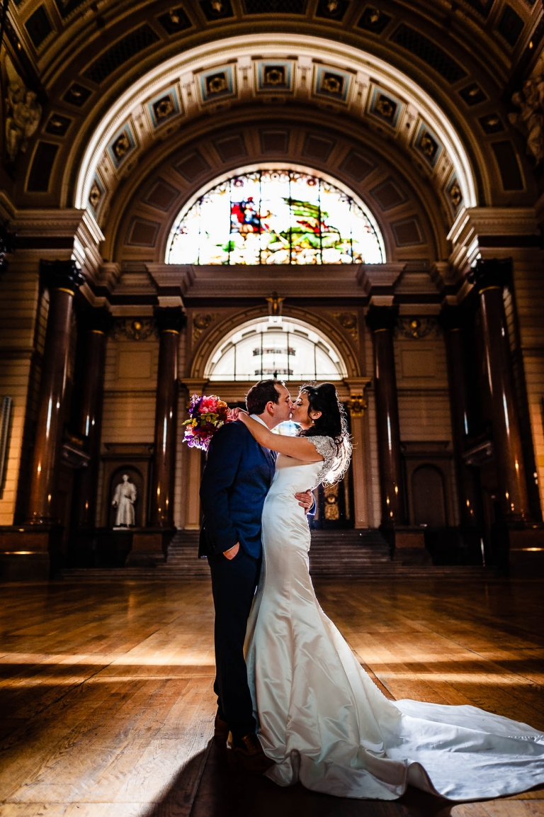 Bride and groom kiss in St Georges hall