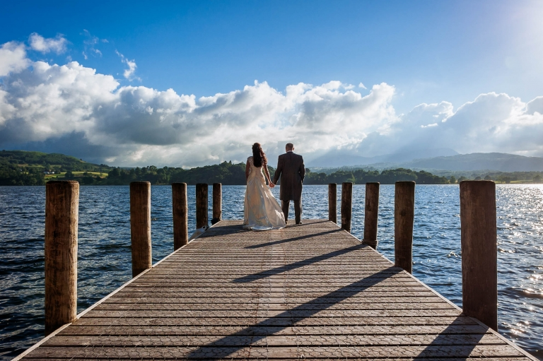 Bride and groom look across Lake Windermere
