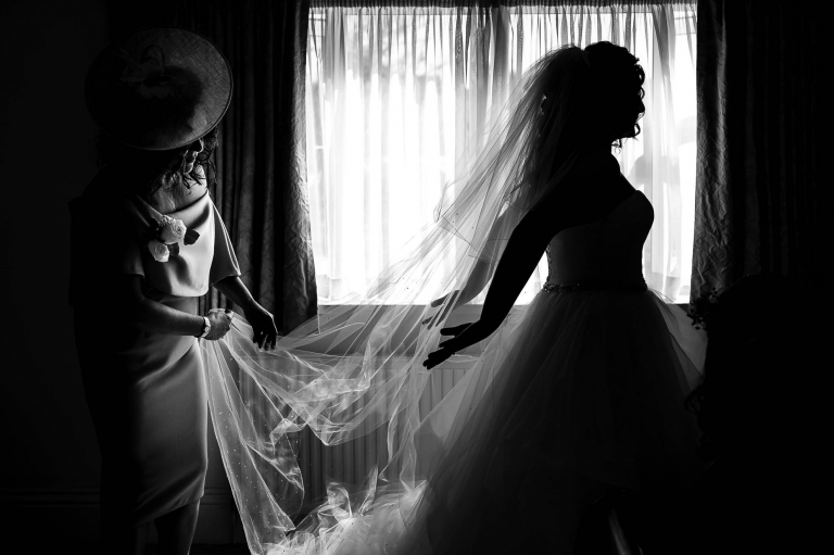 Brides mother adjusts her daughters veil
