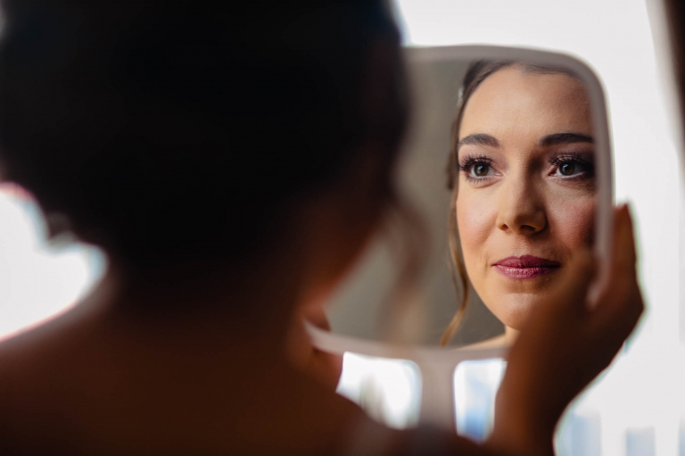 Bride looks at her self in the mirror