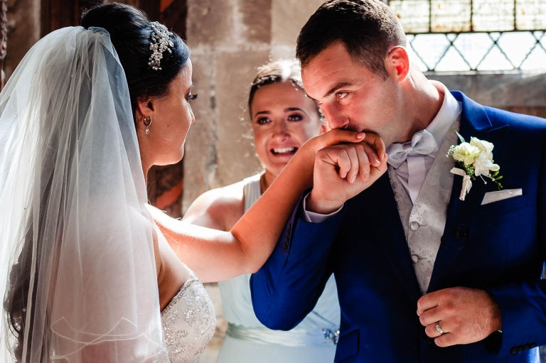 Groom kisses brides ring finger