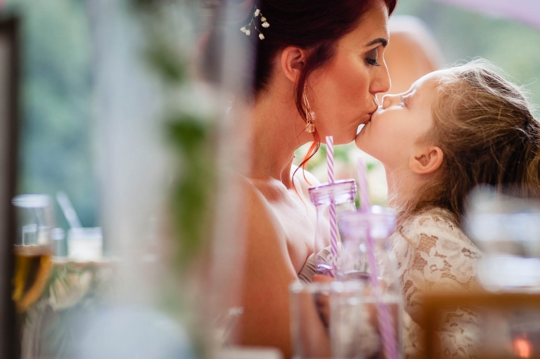 Bridesmaid and daughter kiss