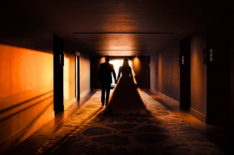 Bride and groom walk down hotel corridor