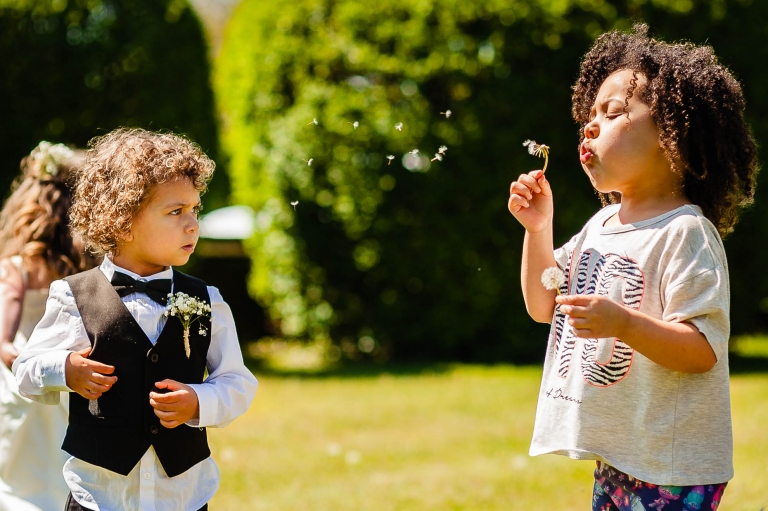Kids playing with dandelions before the wedding ceremony