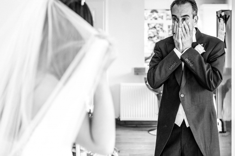 Father of the bride sees the bride in her dress for the first time