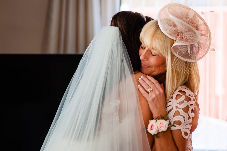 Mother of the bride hugs the bride
