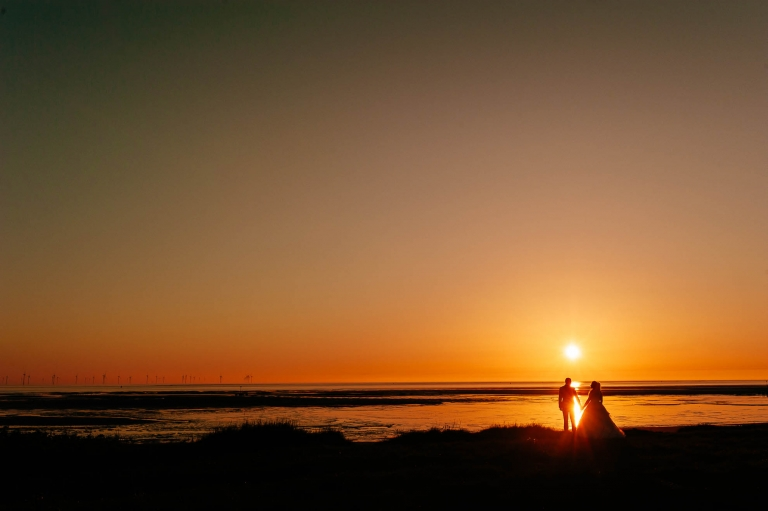 Bride and groom hold hands at sunset