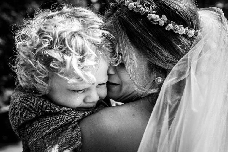 Bride hugs her crying son