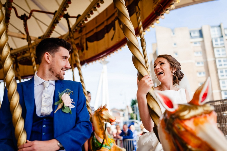 Bride and groom ride a carousel