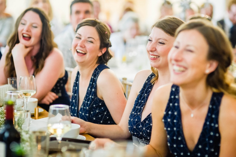 Bridesmaids laugh at grooms speech