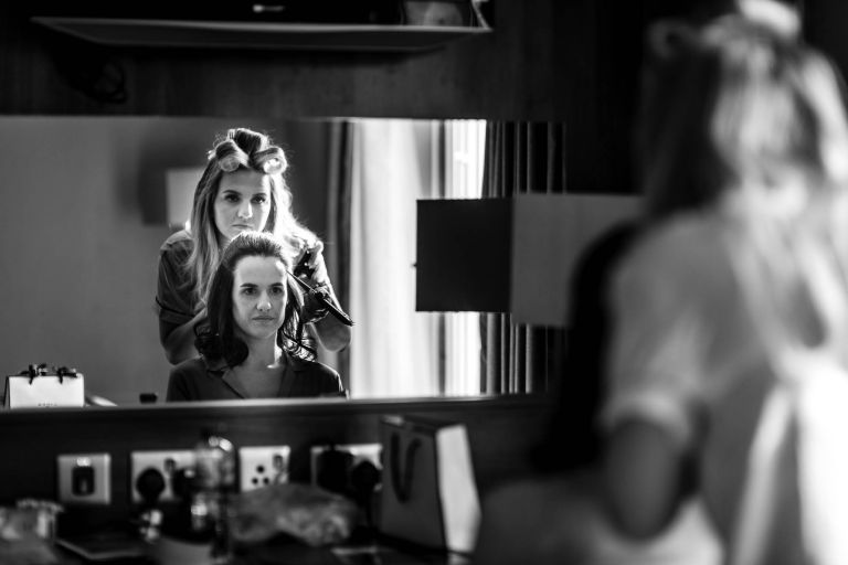 Bride looks in mirror as she has her hair done