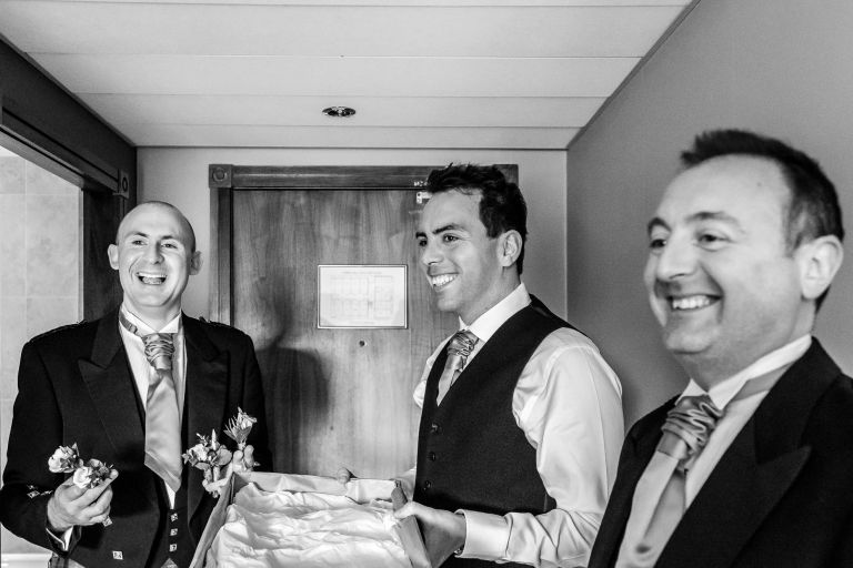 Groom shares a joke with his groomsmen