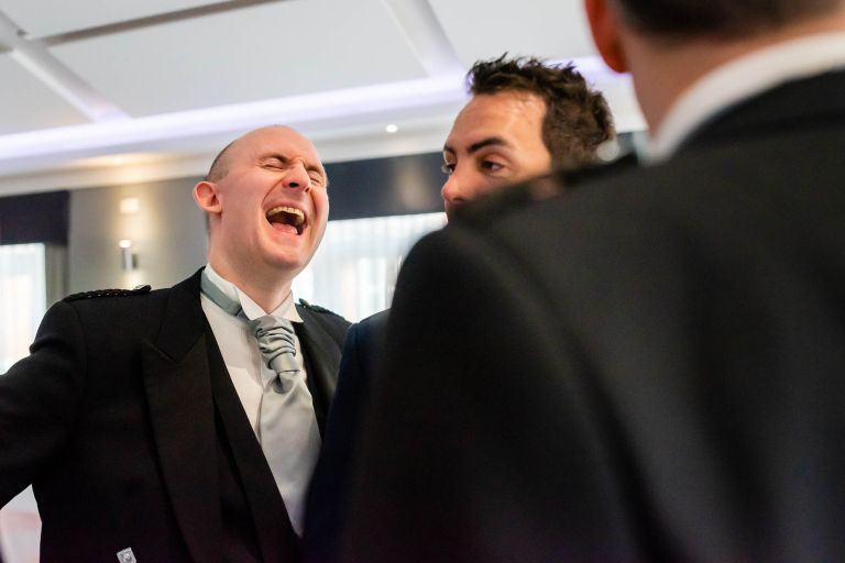 Groom shares a joke with the ushers