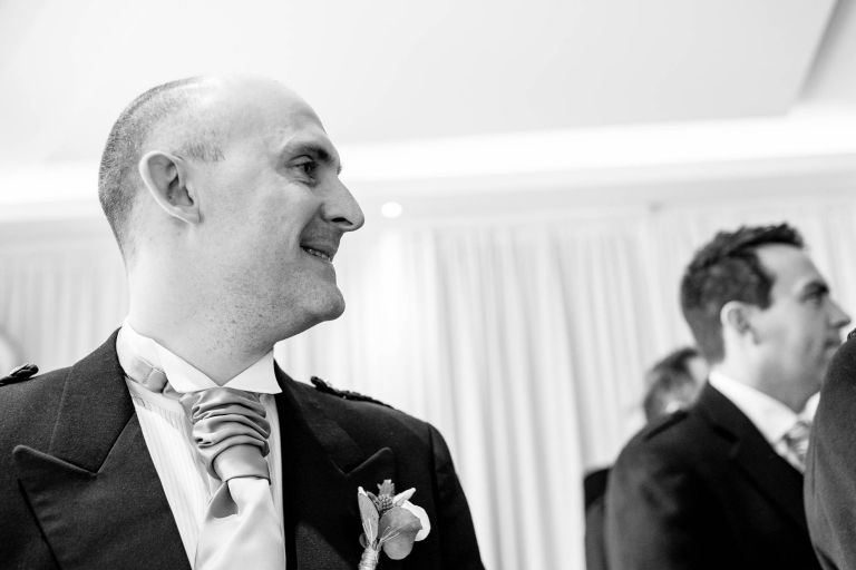 Groom smiles as he watches his bride walk up the aisle