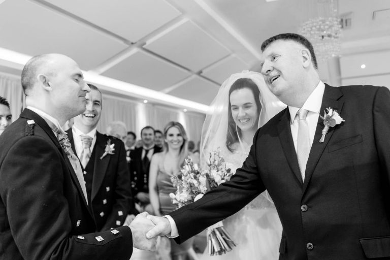 Father of the groom shakes the grooms hand