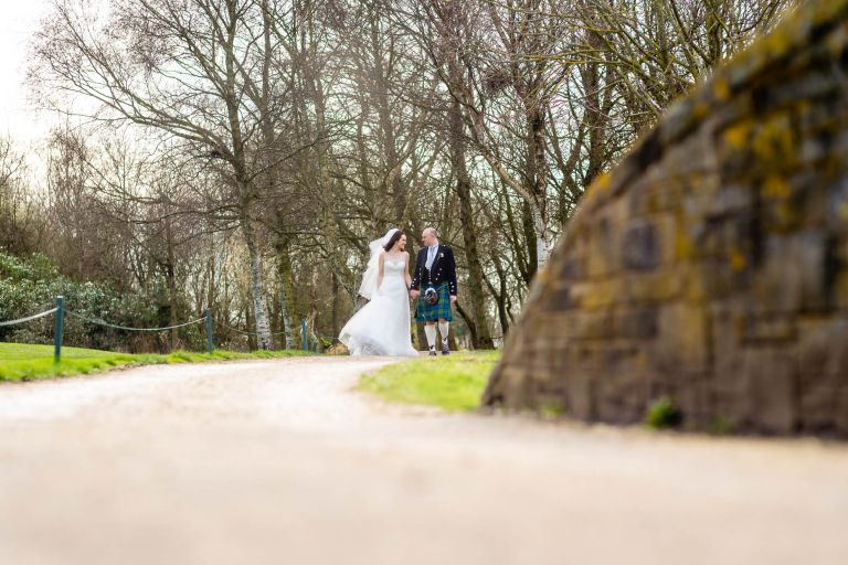 Bride and groom walk towards a bridge hand in hand