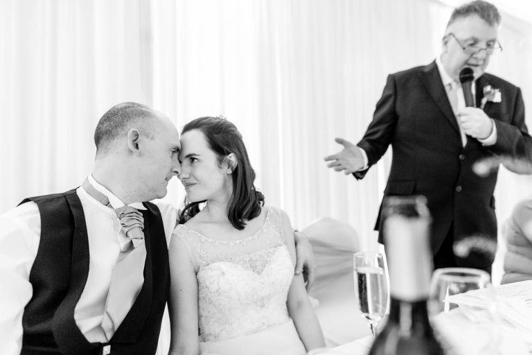 Bride and groom look into each others eyes during father of the grooms speech