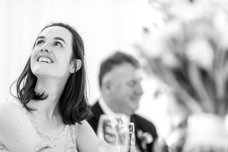 Bride smiles during grooms speech