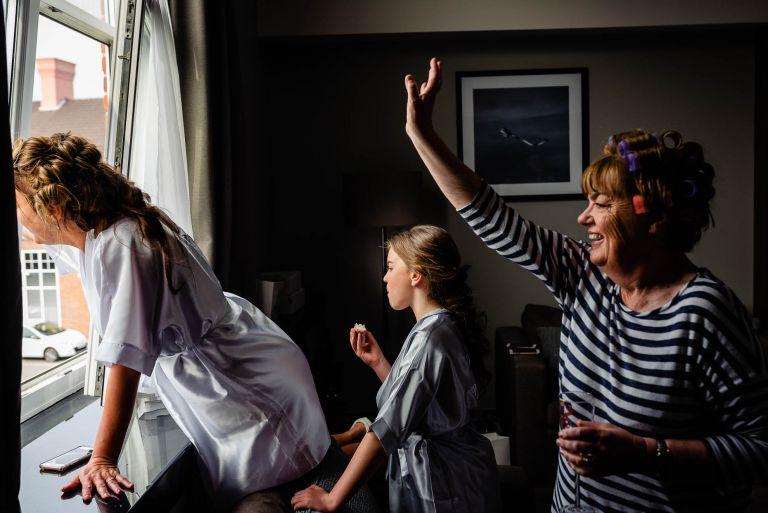 Bride and mum wave at wedding guests
