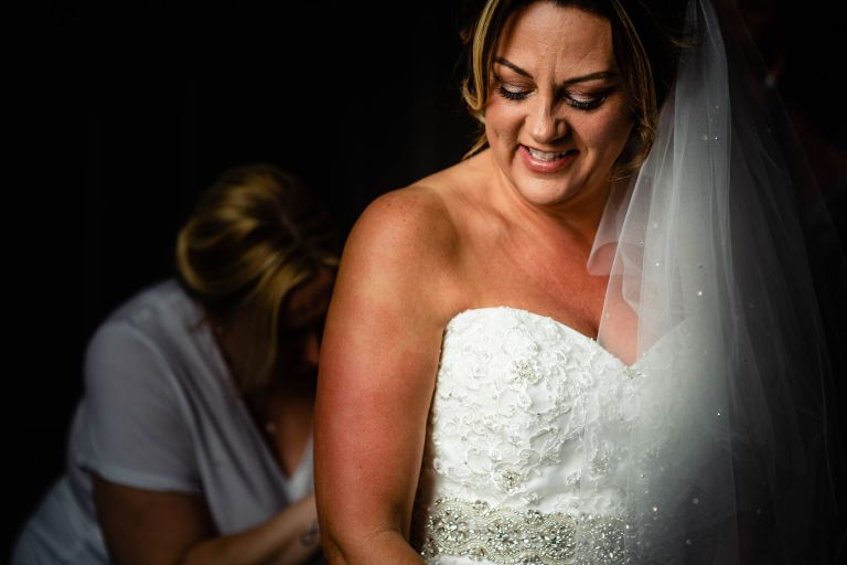Bride smiling as she puts on her wedding dress