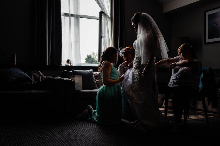 Bride helped into her wedding dress