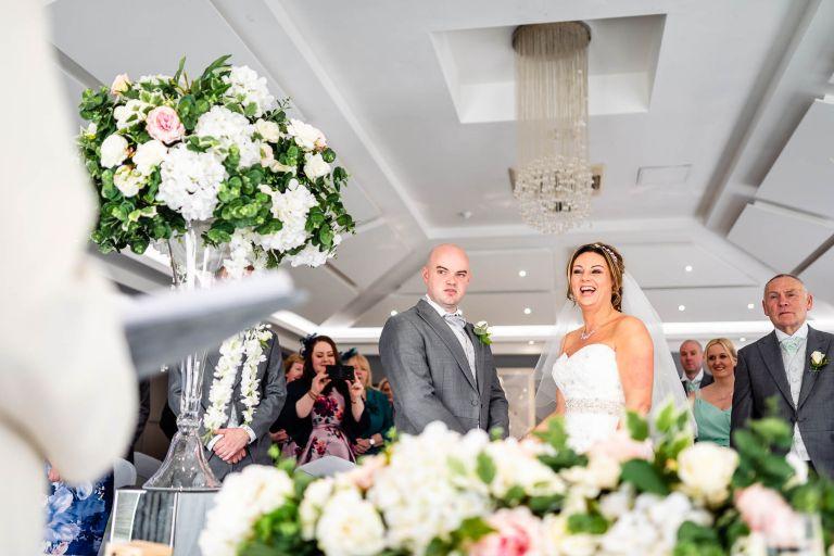 Bride and groom share a joke with registrar