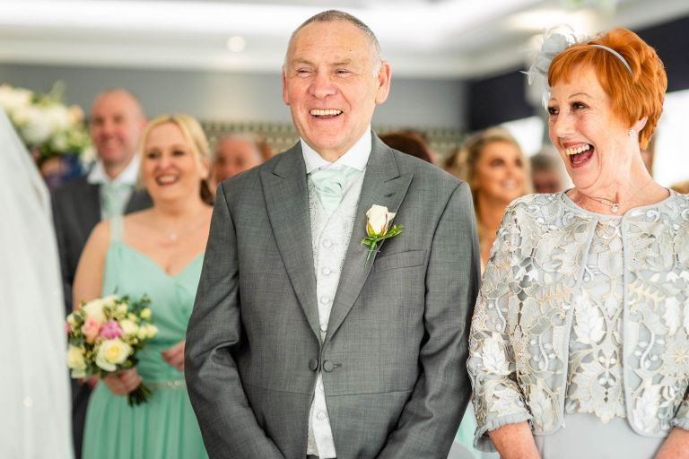 Mother and father of the bride laughing