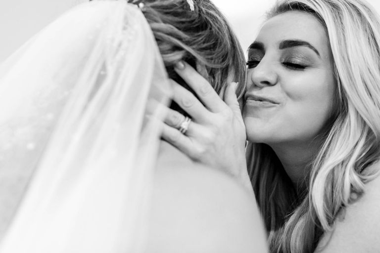 wedding guest gives the bride a kiss on the cheek
