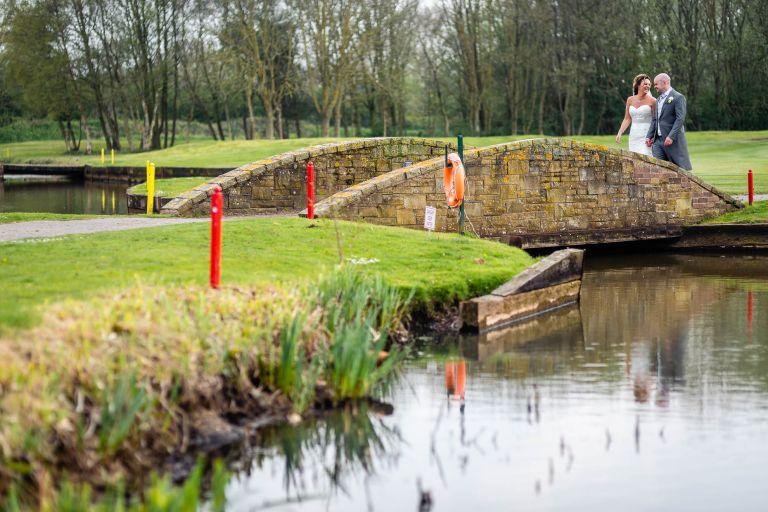 Bride and groom walk towards a bridge