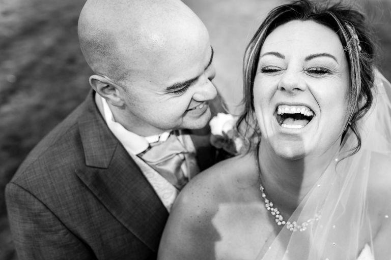 Bride laughs out loud at grooms joke
