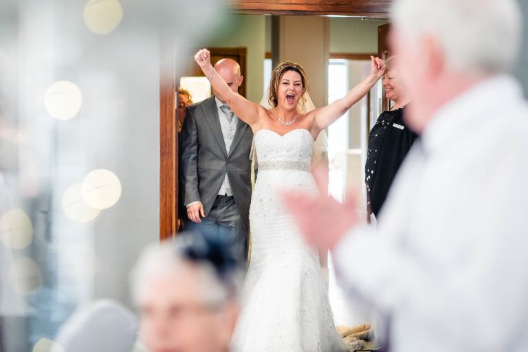 Bride puts her hands in the air as the newlyweds are announced into wedding breakfast