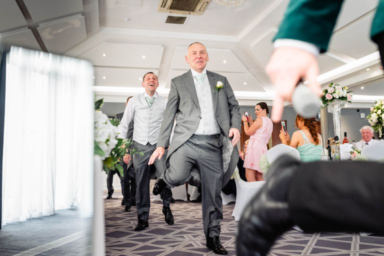 Father of the bride and groomsmen having fun with wedding singer