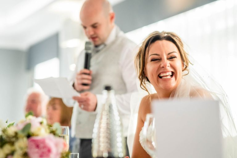 Bride laughing at grooms speech