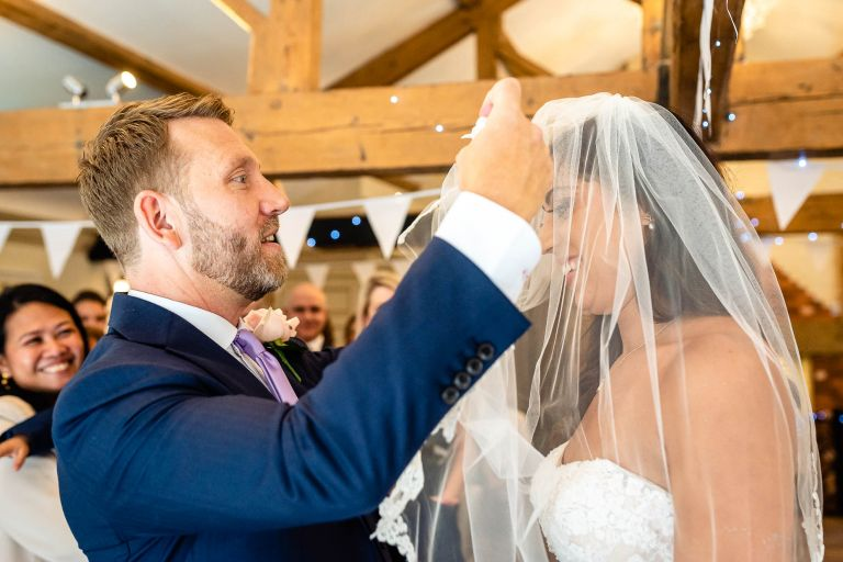 Groom lifts bride's veil