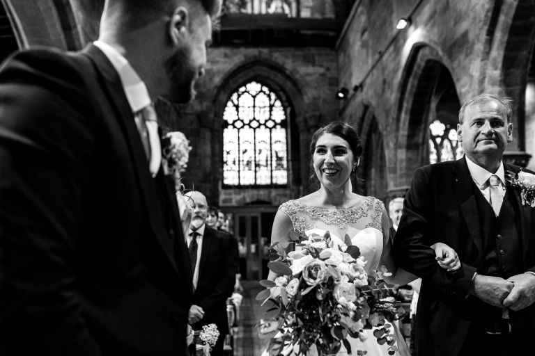 Bride smiles at groom as she arrive at altar