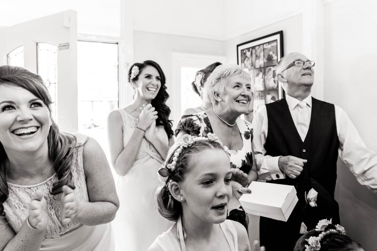 mum and dad and bridesmaids watch bride reveal dress