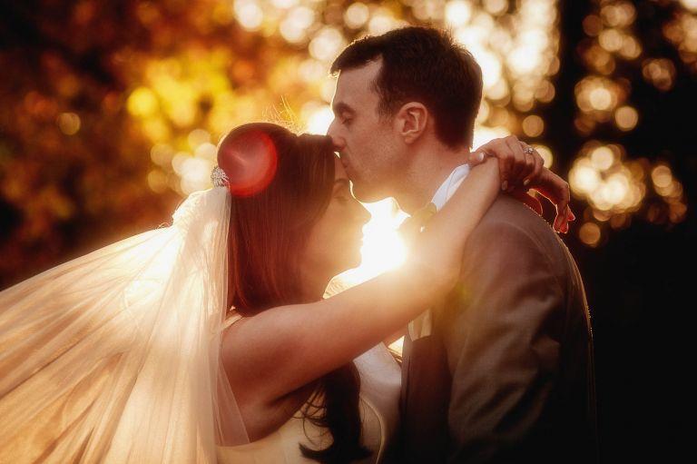 Groom kissing bride on forehead