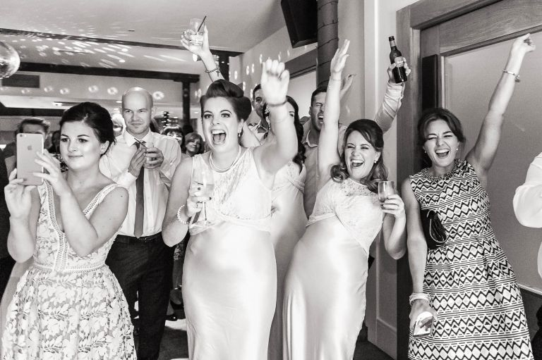 bridesmaids cheer on the newlyweds first dance