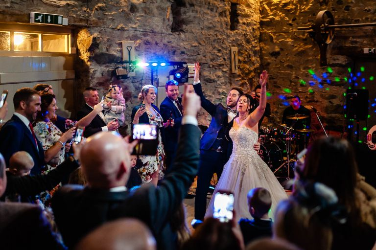bride and groom wave to guests during first dance