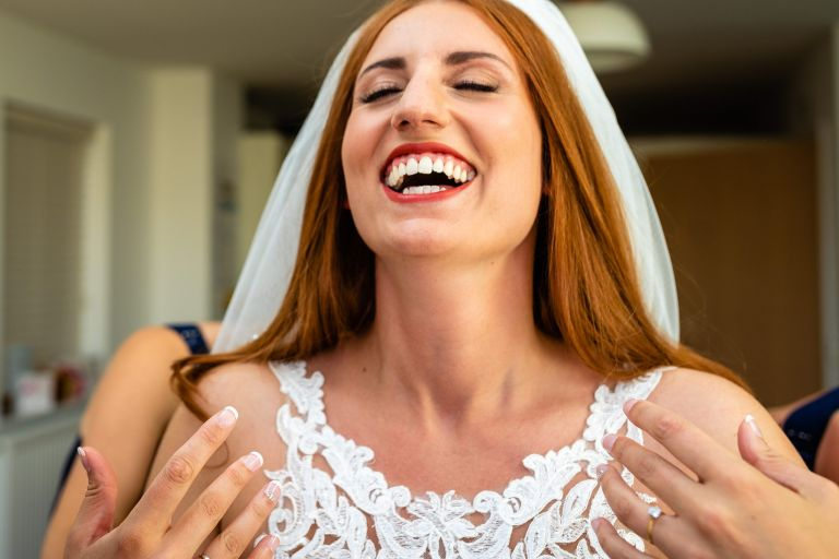 bride laughing as she gets ready
