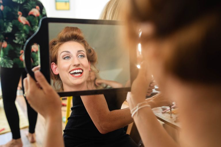 Bride smiles as she looks in mirror