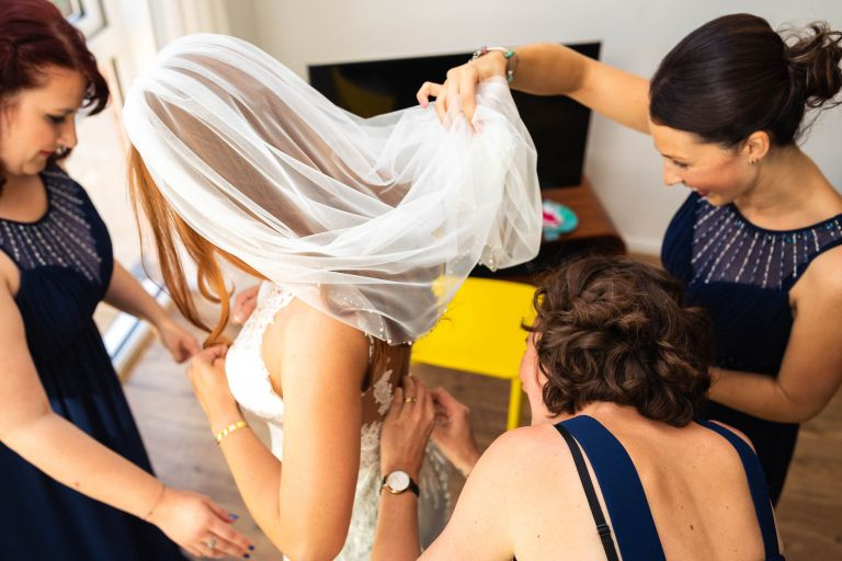 Bride is helped into her dress by bridesmaids