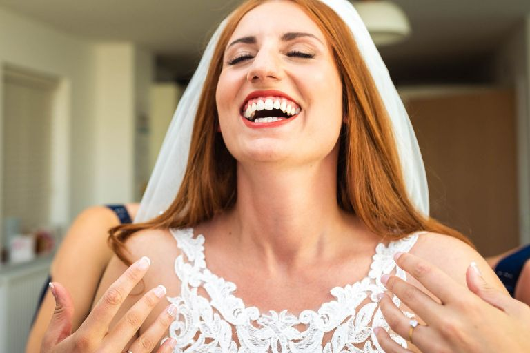 Bride laughs in delight as she puts her dress on
