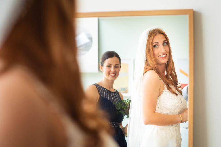Bride admires her dress in the mirror