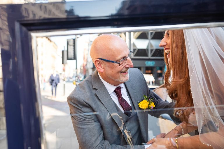 Father of the bride helps the bride out of the wedding car